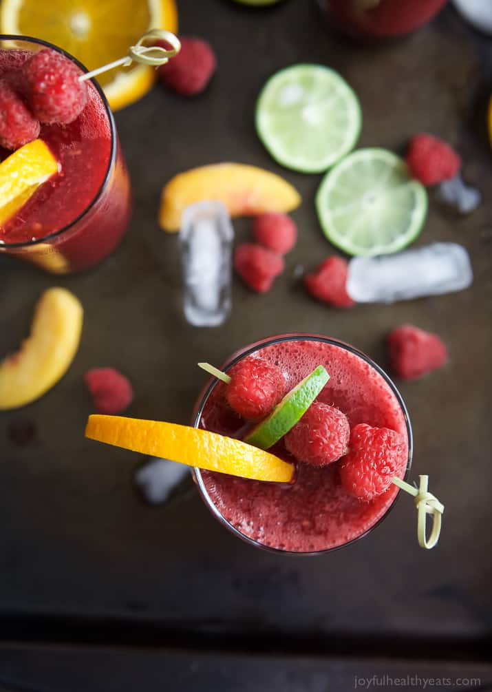 Top view of glasses of Frozen Raspberry Peach Sangria garnished with fruit