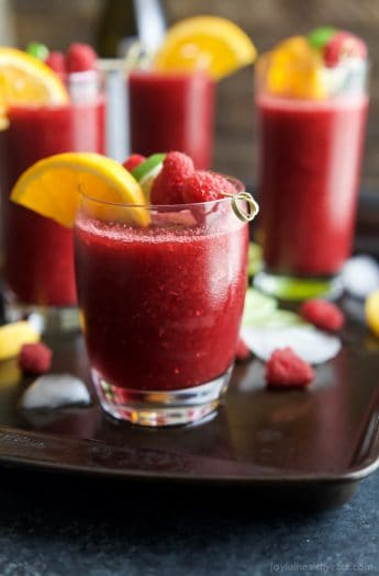 Glasses full of Frozen Raspberry Peach Sangria served with orange wedges and raspberries | joyfulhealthyeats.com