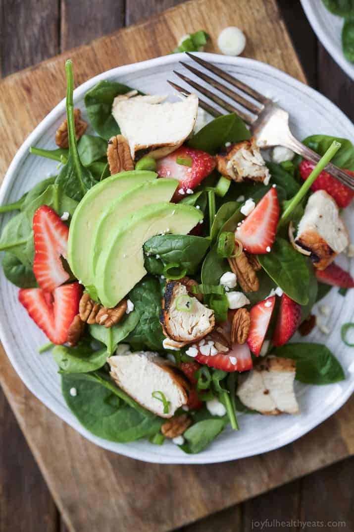 Strawberry Avocado Chicken Salad filled with fresh Berries, Feta, creamy Avocado, and Grilled Chicken. This light salad is topped with a healthy balsamic vinaigrette. The perfect healthy salad option for the summer, bring on the swimsuits! | joyfulhealthyeats.com #glutenfree