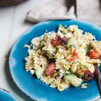 Simple Greek Pasta Salad with cherry tomatoes, artichokes, olives, red onion, cucumber, feta and a homemade dressing! The perfect summer side dish for your next party - I guarantee it will be the first dish to go! | joyfulhealthyeats.com