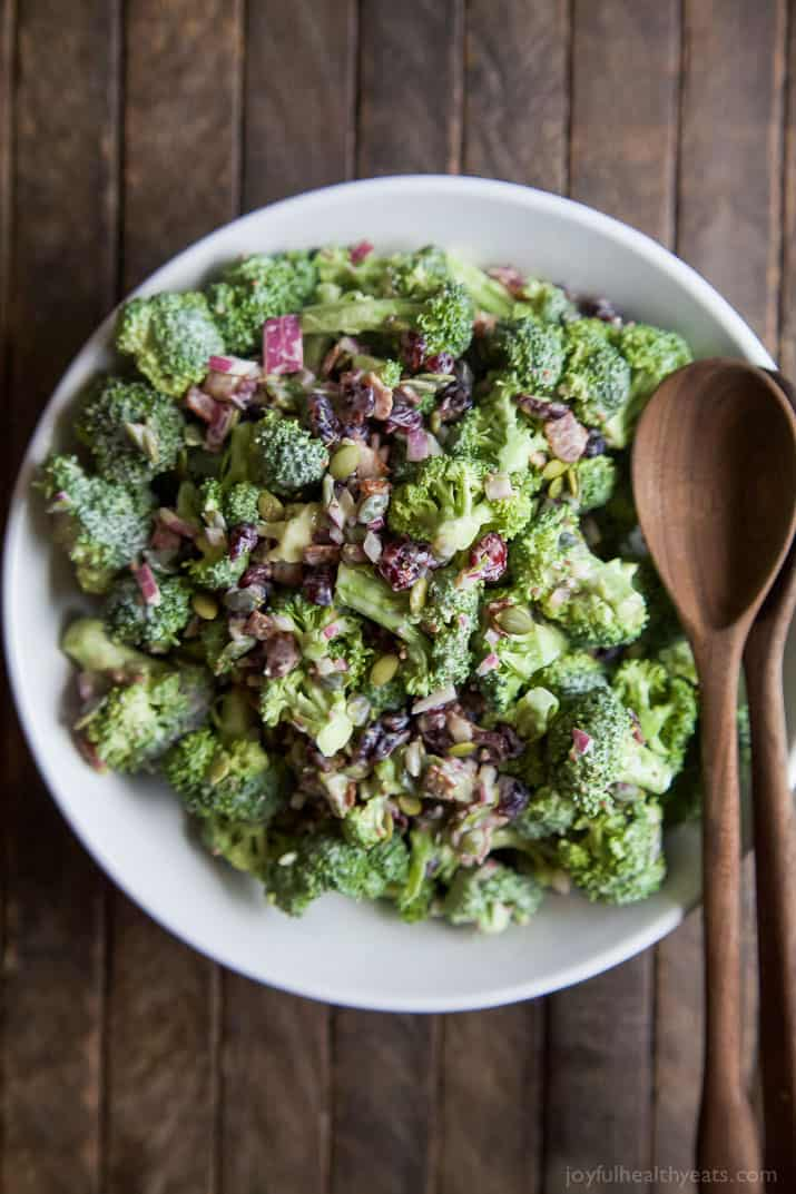 Lightened up Broccoli Salad filled with fresh broccoli, cranberries, red onion, pepitas, BACON, and creamy dressing made with greek yogurt! This salad will be a hit and you'll love the short cut I take! | joyfulhealthyeats.com #glutenfree