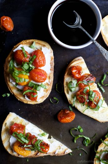 A table with pieces of Roasted Tomato Bruschetta with Whipped Goat Cheese and a bowl of balsamic reduction.