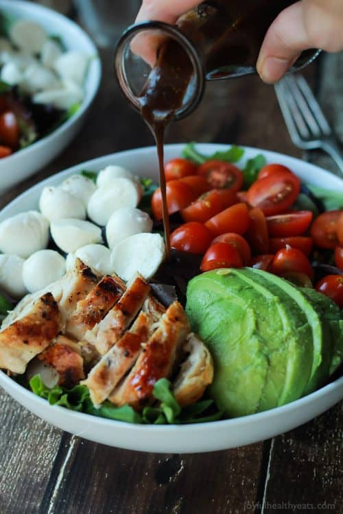 An Avocado Caprese Chicken Salad Being Topped with Balsamic Vinaigrette