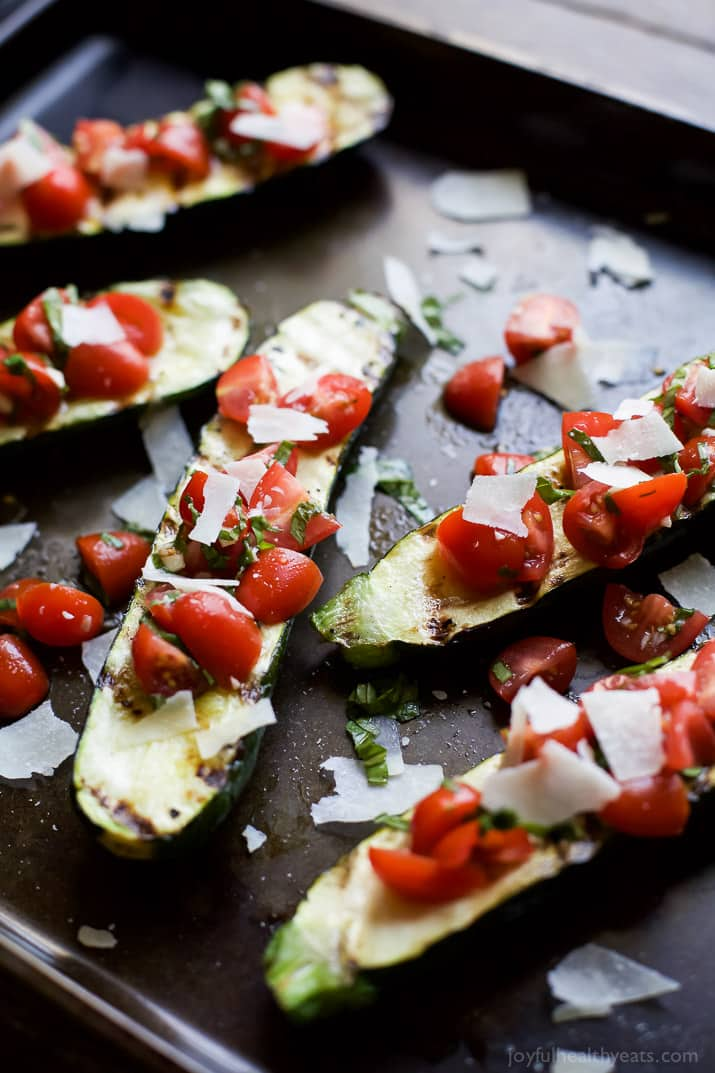 Incredible Crispy and tender Grilled Zucchini topped with a fresh Tomato Basil Bruschetta and Parmesan cheese. The ultimate side dish that will quickly become a family favorite! | joyfulhealthyeats.com #glutenfree #vegetarian