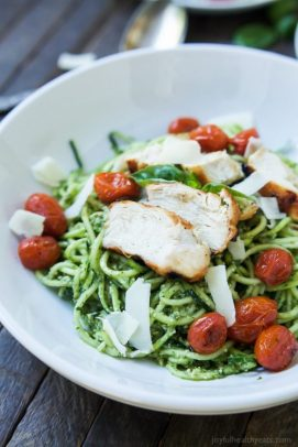 A Bowl of Pesto Chicken Zoodles with Burst Tomatoes on a Picnic Table