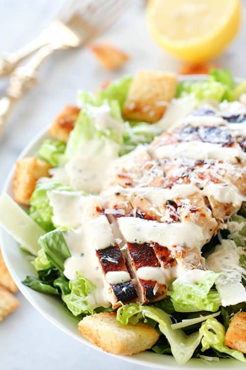 Grilled Chicken Caesar Salad – with a simple marinade recipe, this grilled chicken is tender and delicious! Served over romaine, shaved parmesan, homemade croutons & Caesar Dressing