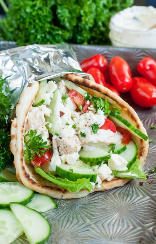 A Greek Chicken Gyro Pita Wrap Wrapped in Tinfoil on an Outdoor Table