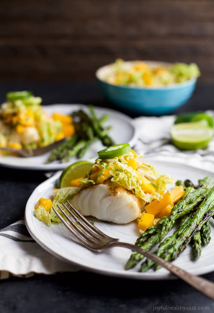 Grilled White Fish topped with Mango Jalapeno Coleslaw next to Asparagus on a plate