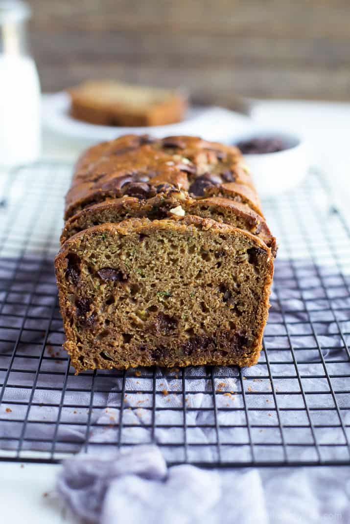 A partially slice loaf of Chocolate Chip Zucchini Bread on a cooling rack