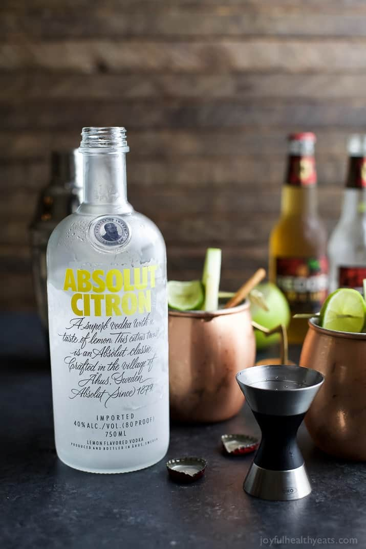 A bottle of Absolut Citron next to copper mugs of apple cider moscow mules