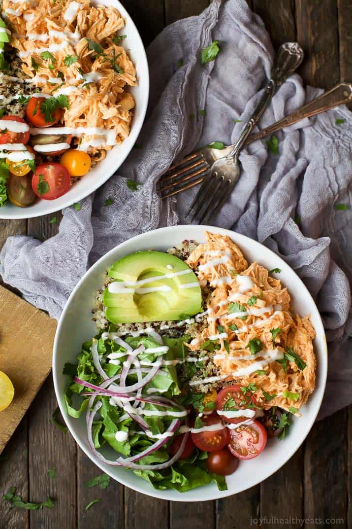 Top view of Buffalo Chicken Quinoa Bowls topped with avocado, tomato, shredded buffalo chicken, drizzled with ranch and served on a bed of quinoa.