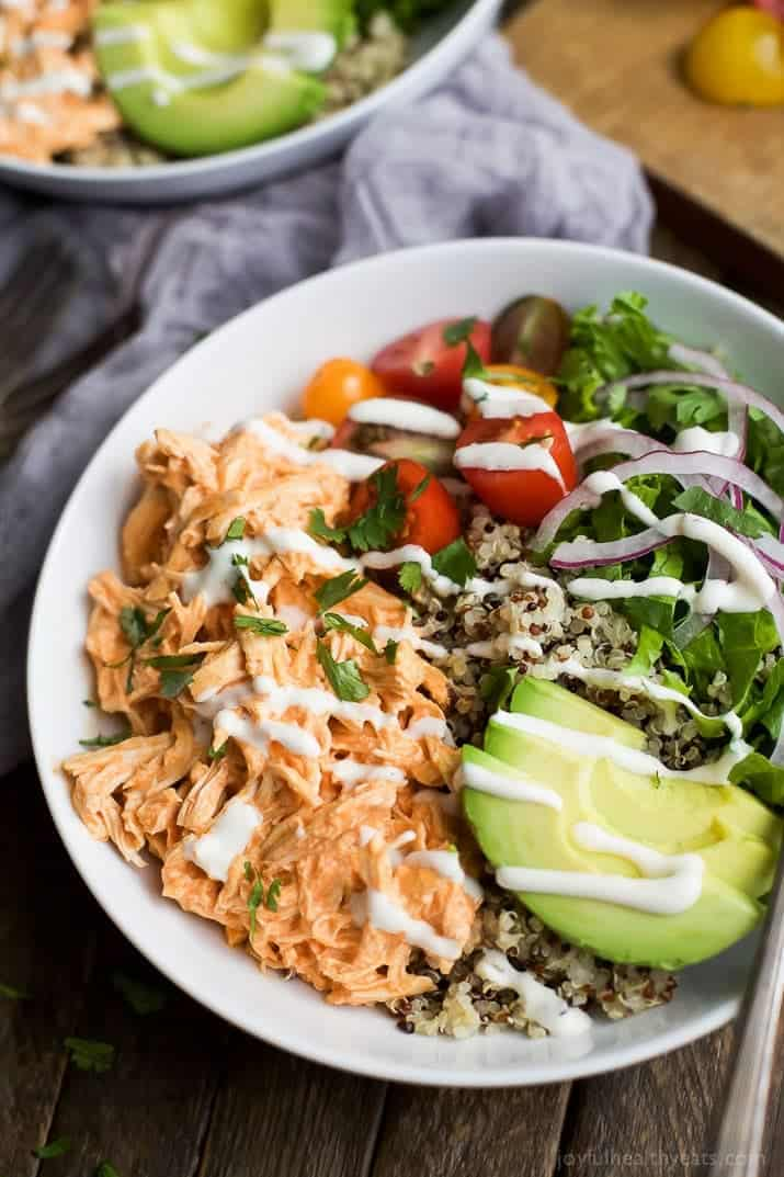 Buffalo Chicken Quinoa Bowls topped with avocado, tomato, shredded buffalo chicken, drizzled with ranch and served on a bed of quinoa