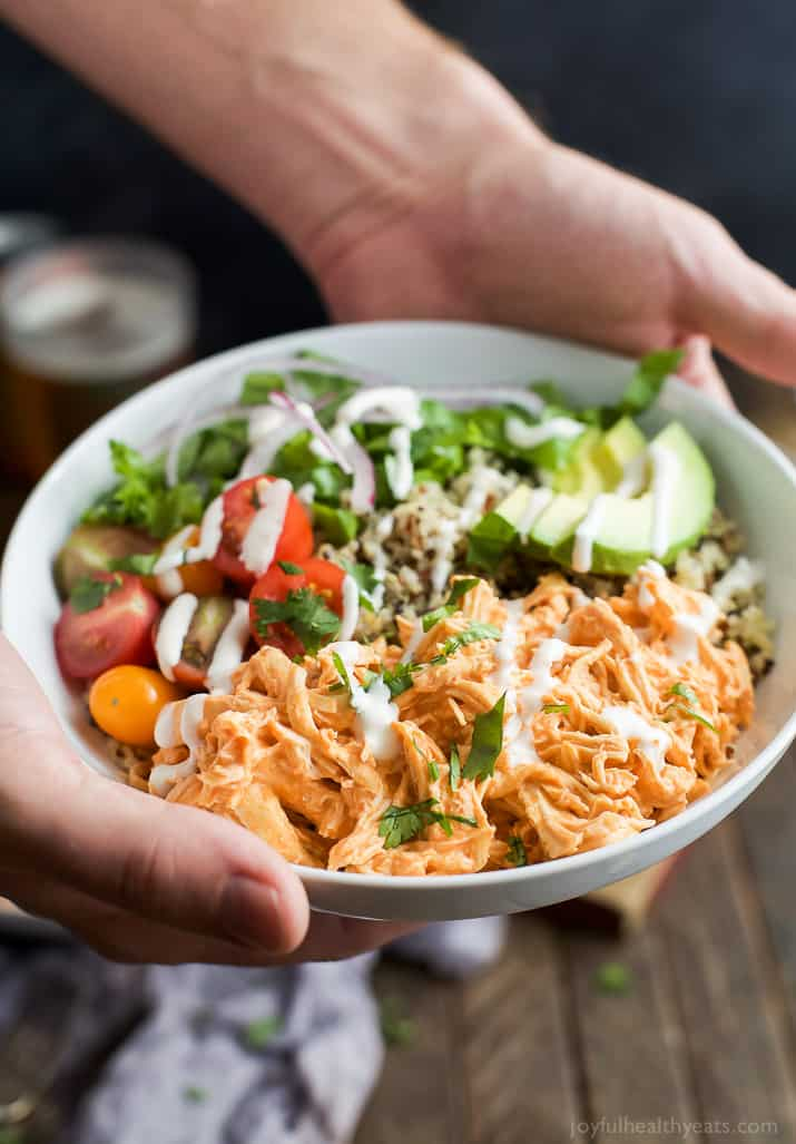 Hands holding a Buffalo Chicken Quinoa Bowl topped with avocado, tomato, shredded buffalo chicken, drizzled with ranch and served on a bed of quinoa