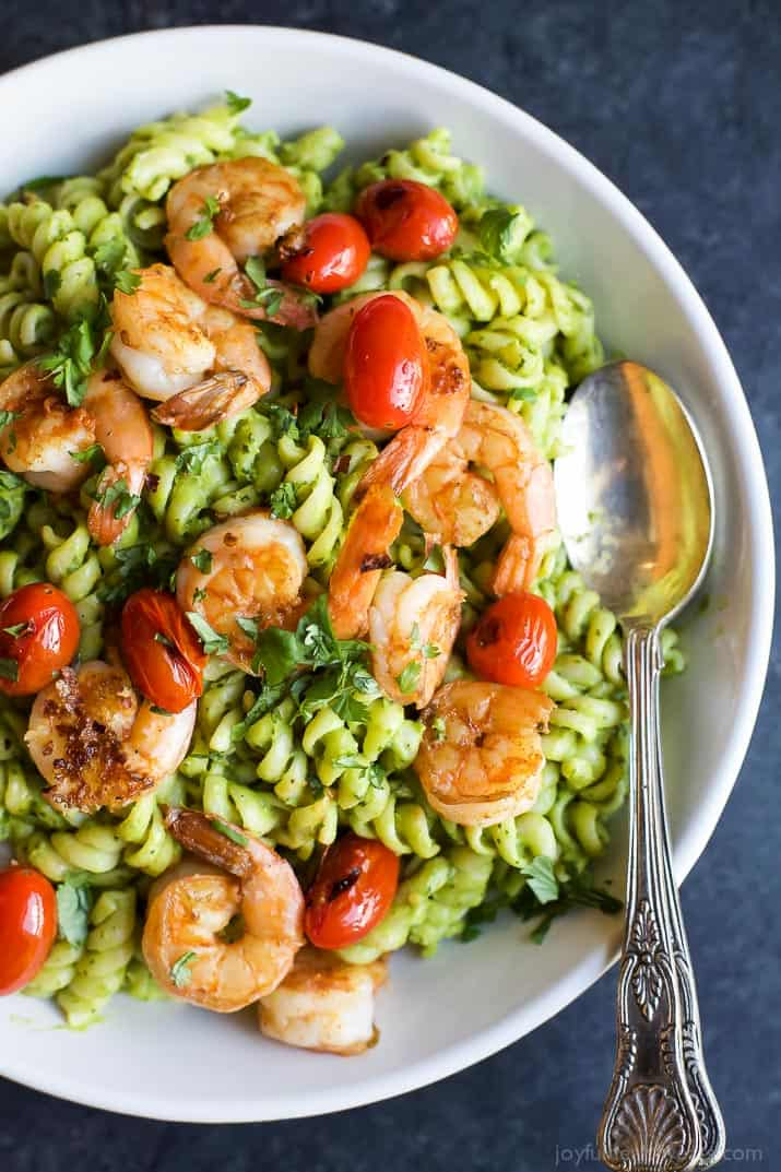 Top view of a bowl of Chimichurri Avocado Pasta with Pan Seared Shrimp and grape tomatoes