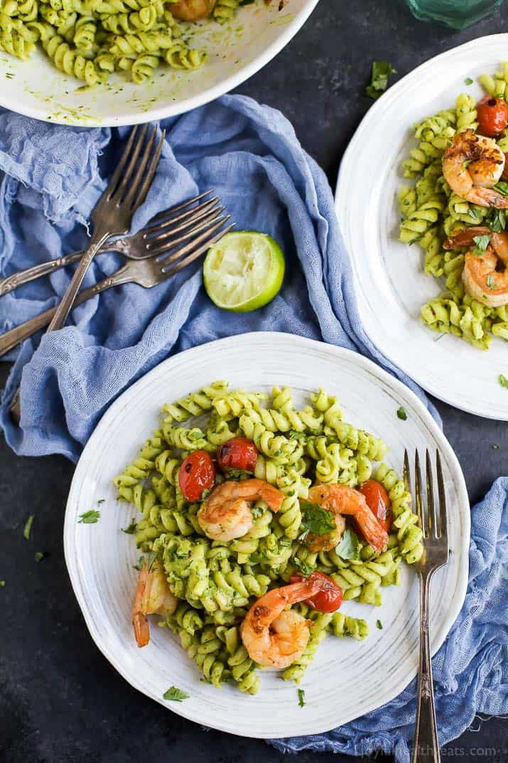 Overhead view of plates of Chimichurri Avocado Pasta with Pan Seared Shrimp and grape tomatoes