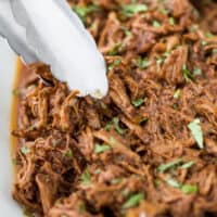 tongs picking up slow cooker barbacoa short rib tacos