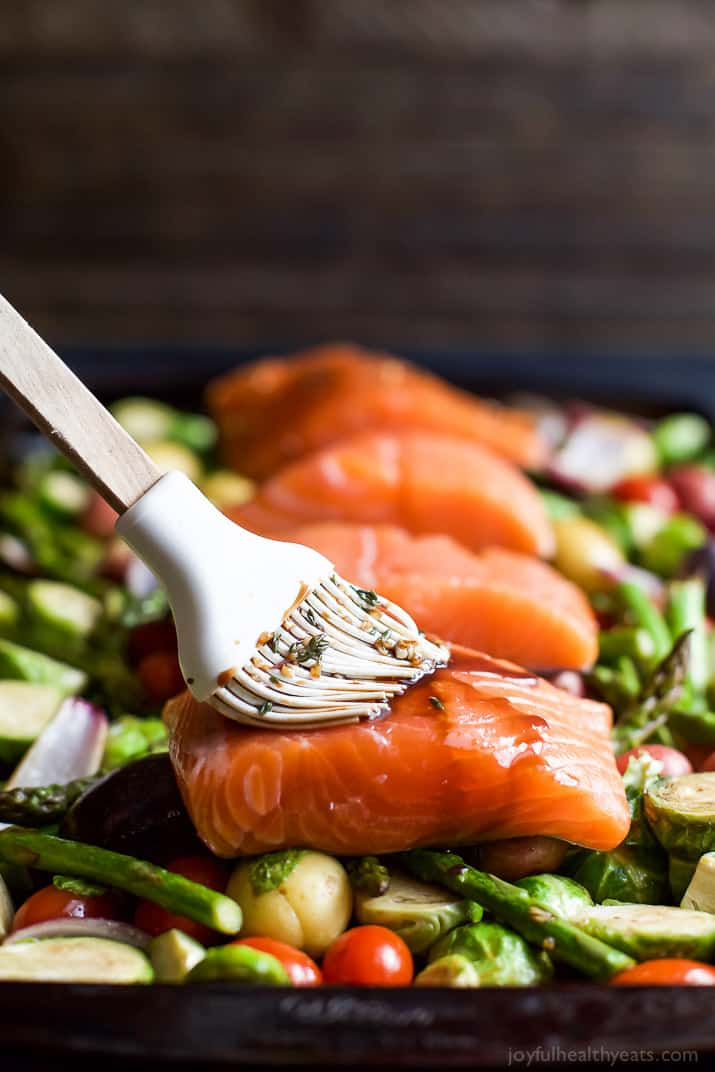 Sheet Pan Salmon on a bed of potatoes, asparagus, and brussels sprouts being brushed with balsamic