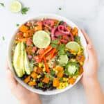 hands holding easy sweet potato black bean quinoa bowls with crema