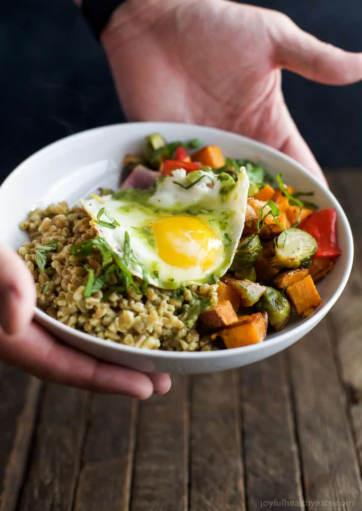 Hands holding a Harvest Roasted Vegetable Grain Bowl topped with an egg