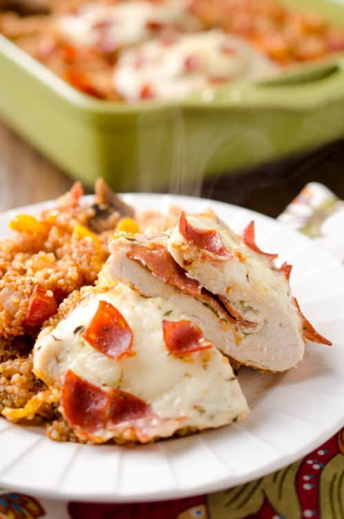 Pizza Stuffed Chicken Quinoa Bake is a hearty but healthy casserole filled with fluffy quinoa and your favorite pizza toppings along with garlic herb cheese and pepperoni stuffed chicken breasts for a dinner recipe the whole family will love!
