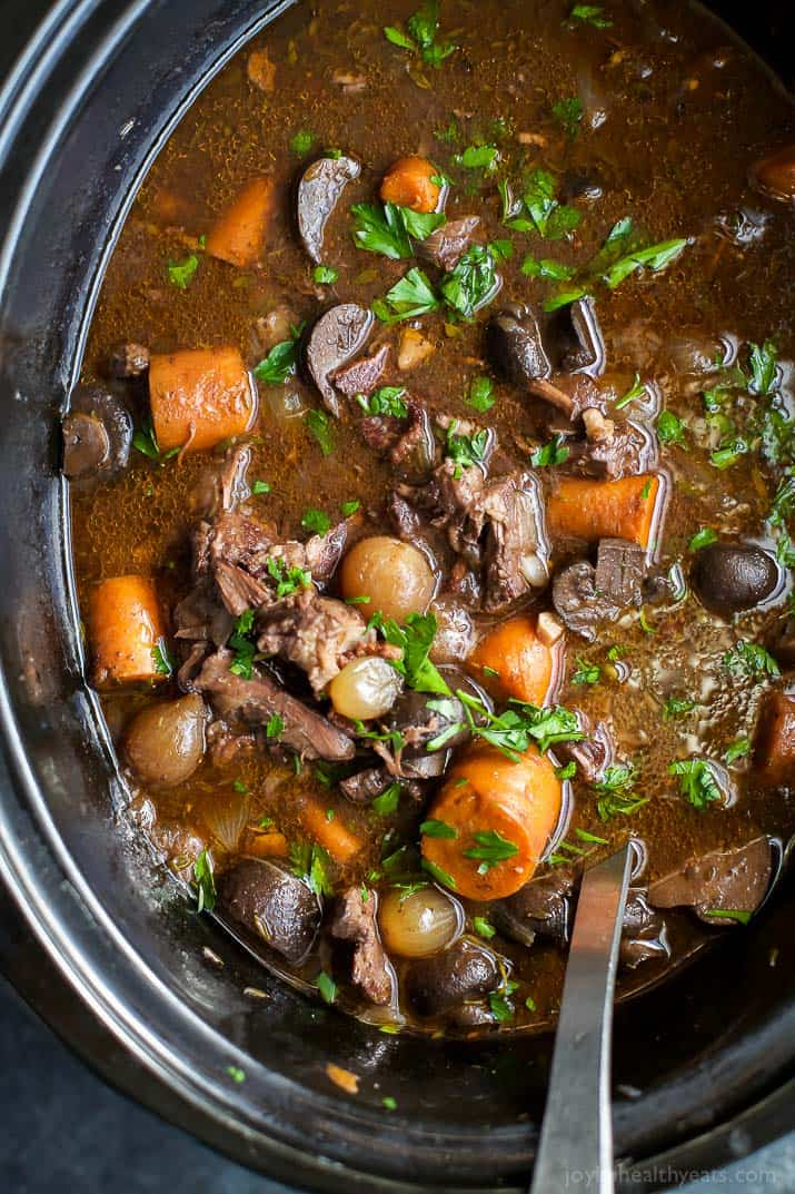 A slow cooker of beef bourguignon with fresh herbs on top