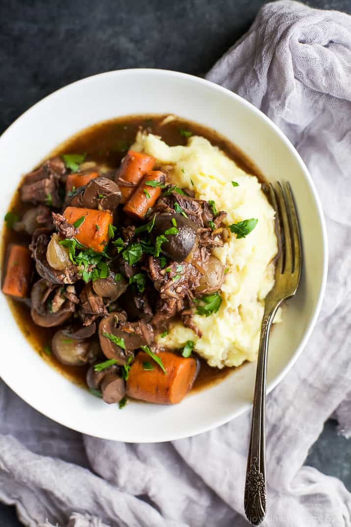 A white bowl of Beef Bourguignon with mashed potatoes