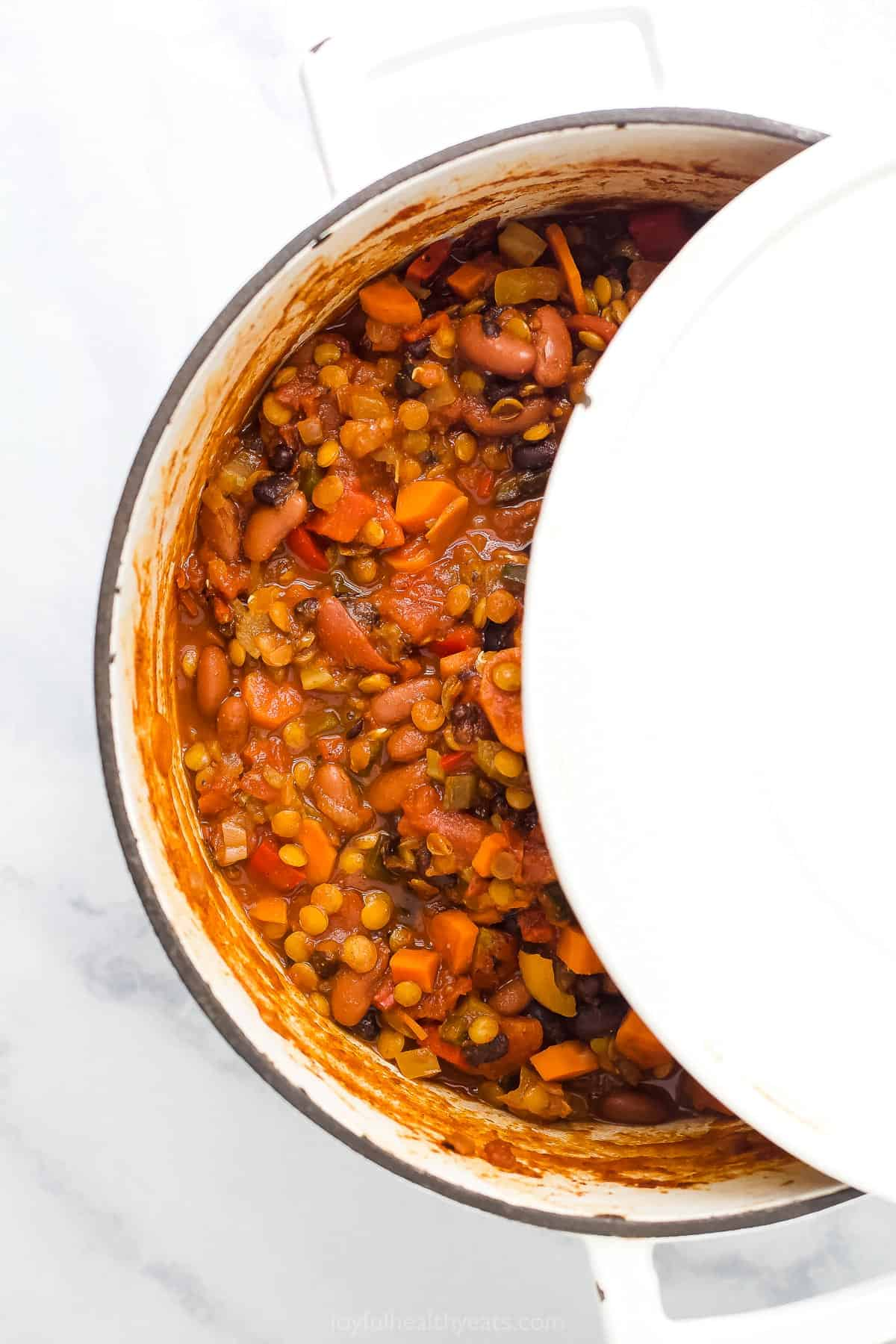 vegetarian lentil chili in a dutch oven with top partly on
