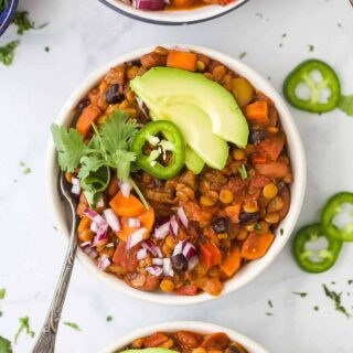 vegetarian lentil chili in a bowl with toppings