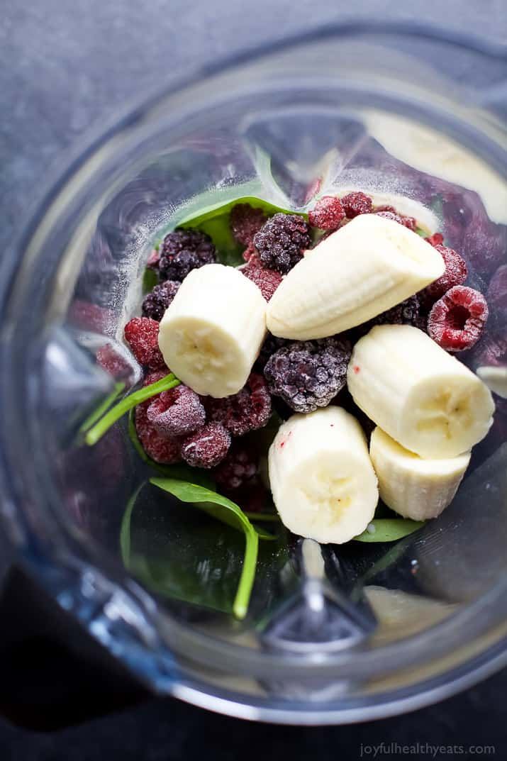 Banana chunks, frozen berries and spinach in a blender jar