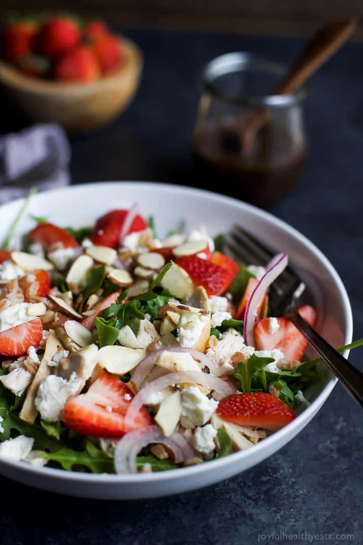 FARRO ARUGULA STRAWBERRY CHICKEN SALAD in a bowl topped with sliced almonds and goat cheese