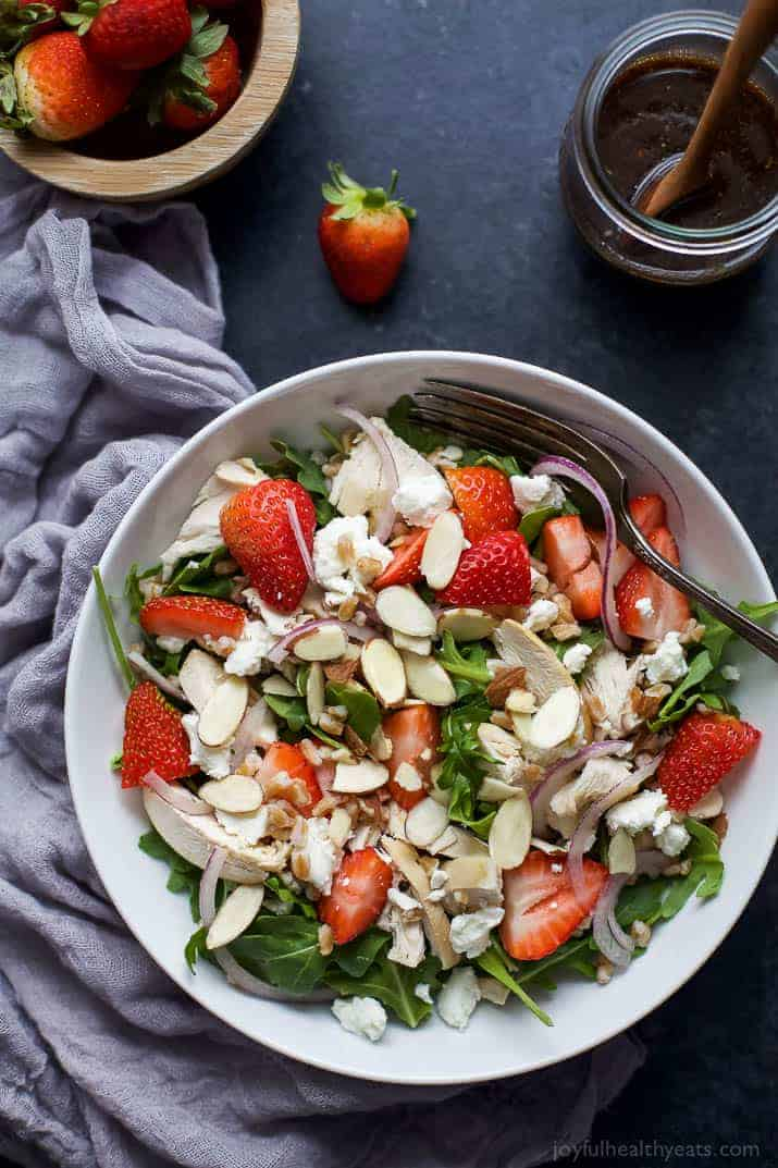 Top view of Farro Arugula Strawberry Chicken Salad with sliced almonds and goat cheese in a bowl
