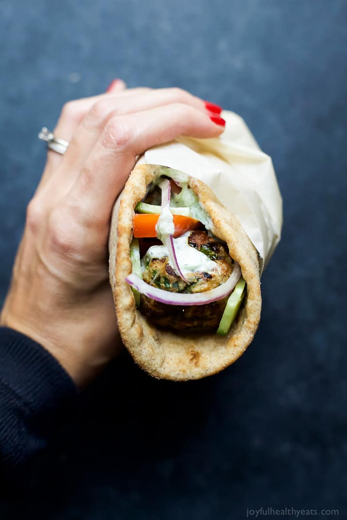 A hand holding a Greek Turkey Meatball Gyro