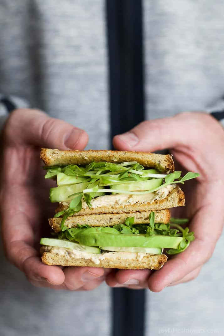 Two halves of Cucumber Avocado Sandwich stacked in a person's hands