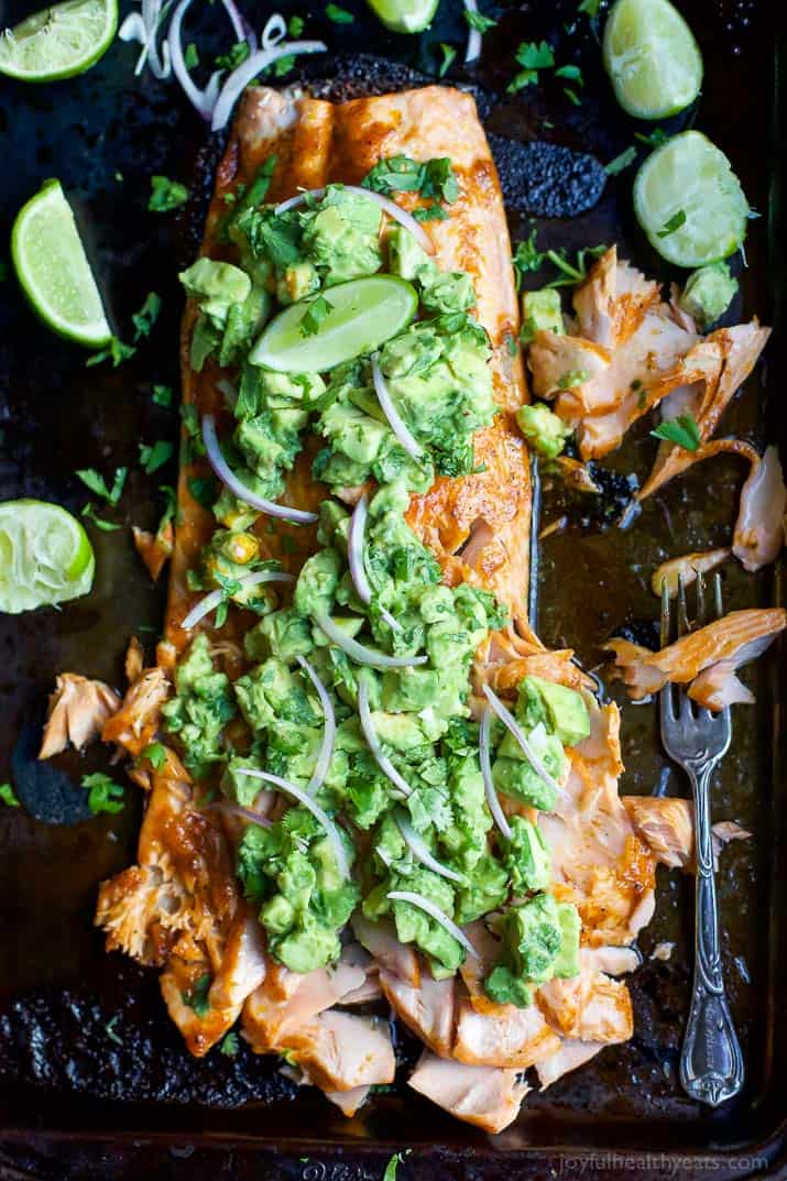 Paleo Baked Salmon that's rubbed down with a sweet & spicy spice blend then topped with a fresh zesty Avocado Salsa! This easy healthy recipe is done in less than 30 minutes!   joyfulhealthyeats.com