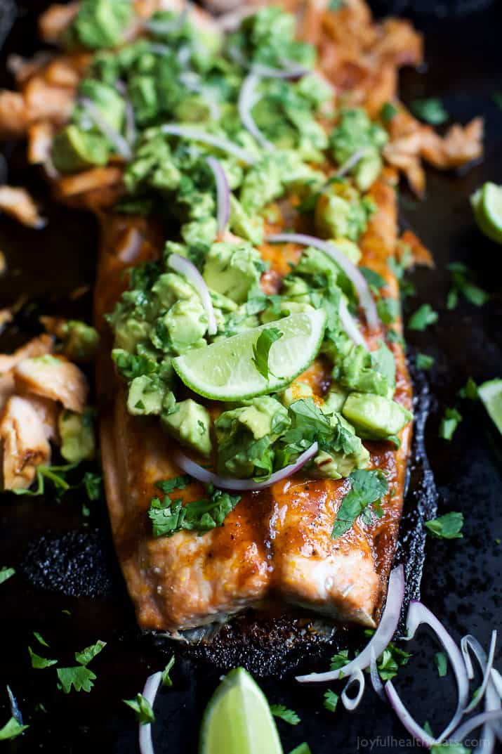 Paleo Baked Salmon that's rubbed down with a sweet & spicy spice blend then topped with a fresh zesty Avocado Salsa! This easy healthy recipe is done in less than 30 minutes! | joyfulhealthyeats.com