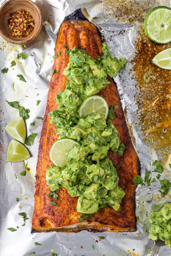 baked salmon in foil with avocado salsa on top