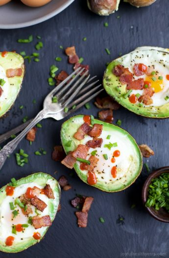 BAKED EGGS IN AVOCADO with crispy bacon and a Sriracha drizzle! The ultimate Paleo Breakfast, high in protein & fiber and loaded with flavor! I guarantee you'll be addicted after the 1st bite! | joyfulhealthyeats.com