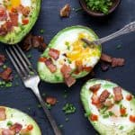 baked eggs in an avocado topped with crispy bacon