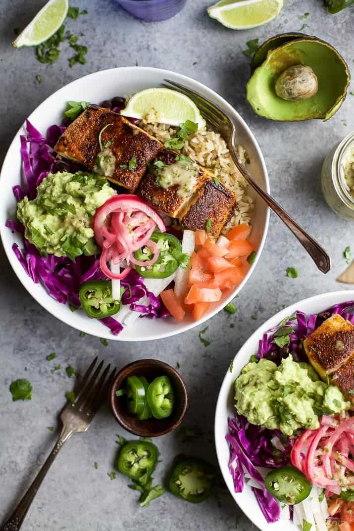 Top view of Fish Taco Rice Bowls with avocado and pickled onions, topped with a Cilantro Lime Dressing
