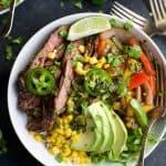 steak fajita burrito bowls in a bowl topped with avocado