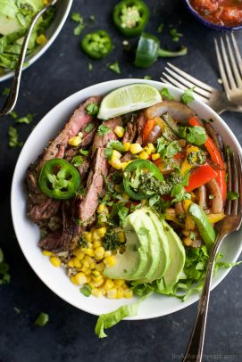 steak fajita burrito bowls in a bowl topped with avocado
