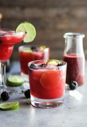 Thyme Blackberry Margaritas in different shaped glasses with limes and blackberries