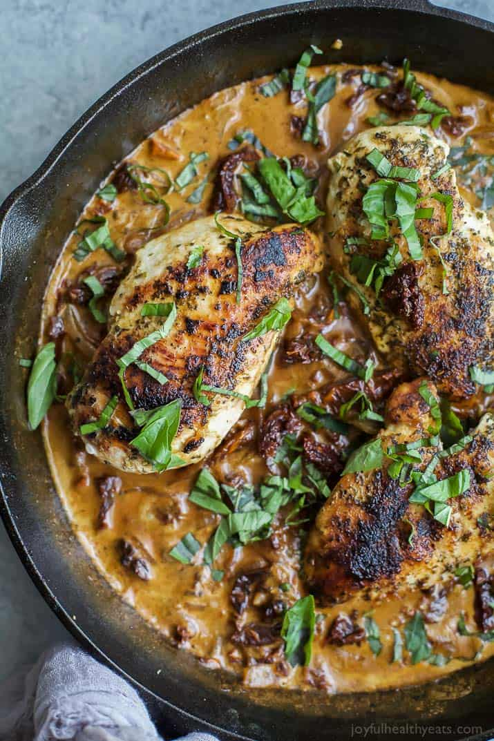 Chicken breasts in creamy sundried tomato sauce in a skillet topped with fresh herbs
