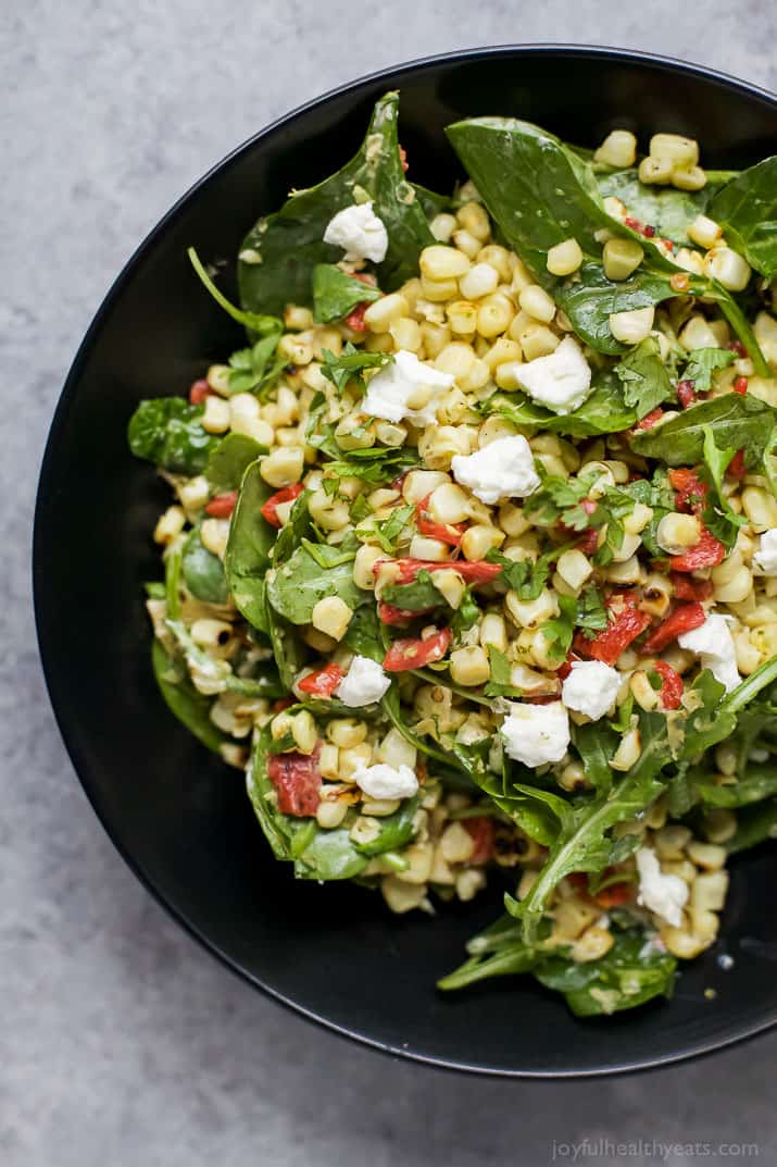 Top view of GRILLED CORN SALAD with fresh greens, roasted red pepper, and goat cheese