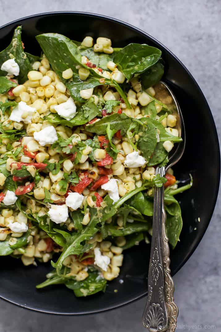 Top view of GRILLED CORN SALAD with fresh greens, roasted red pepper, and goat cheese in a bowl