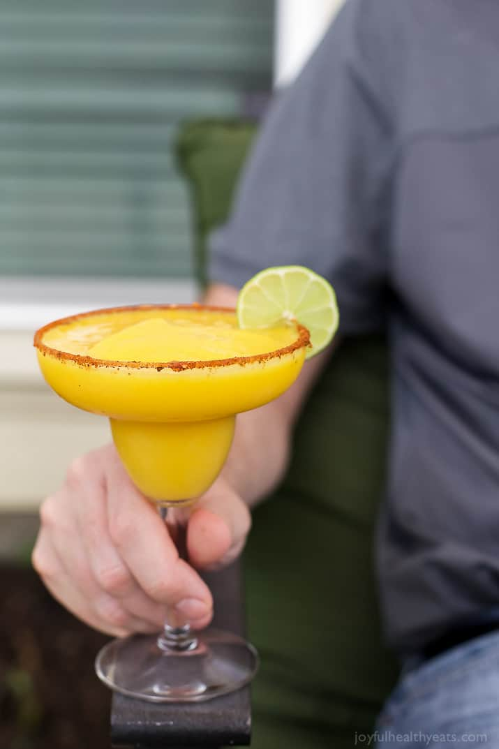 A hand holding a glass of Frozen Mango Margarita with a chili lime salt rim