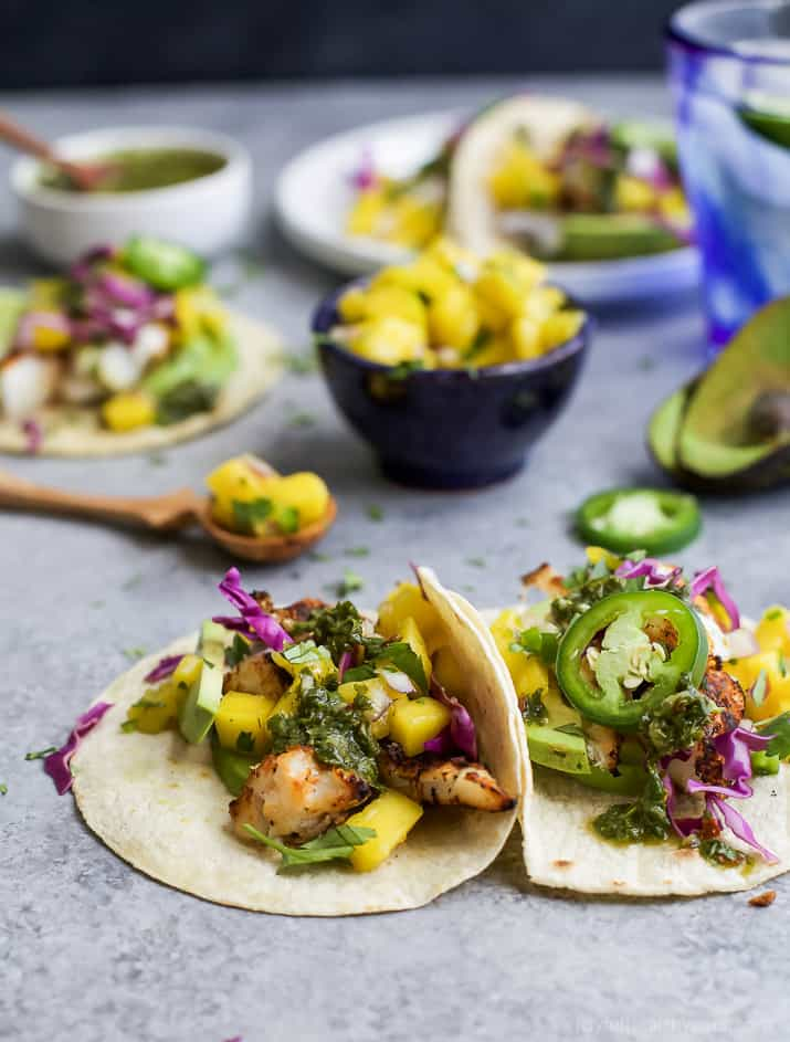 """30 Minute GRILLED FISH TACOS topped with a fresh MANGO SALSA, Avocado, and Chimichurri! This easy grilling recipe is one """"winner"""" of a meal that you're family will fall in love with!   gluten free recipes"""
