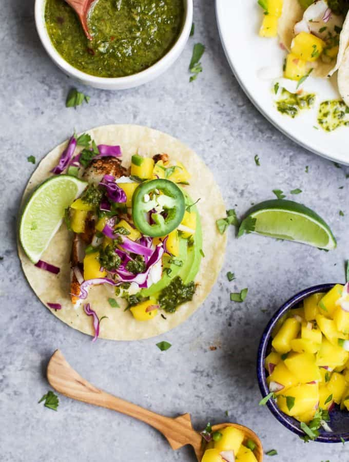 """30 Minute GRILLED FISH TACOS topped with a fresh MANGO SALSA, Avocado, and Chimichurri! This easy grilling recipe is one """"winner"""" of a meal that you're family will fall in love with! 