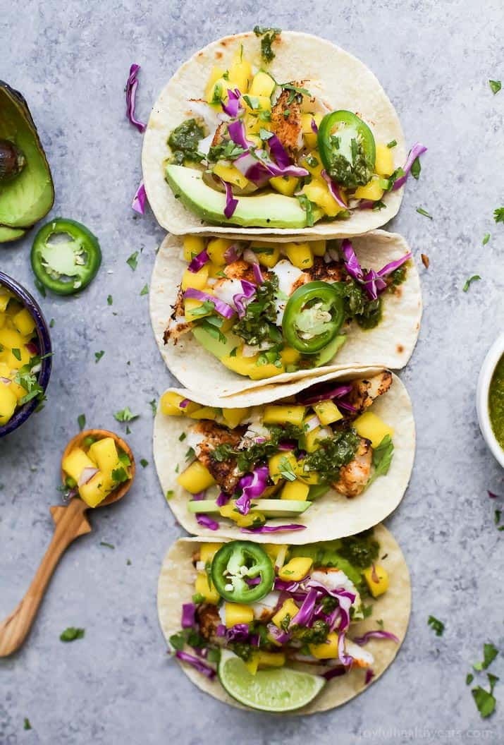 Top view of four GRILLED FISH TACOS topped with fresh MANGO SALSA, Avocado, and Chimichurri