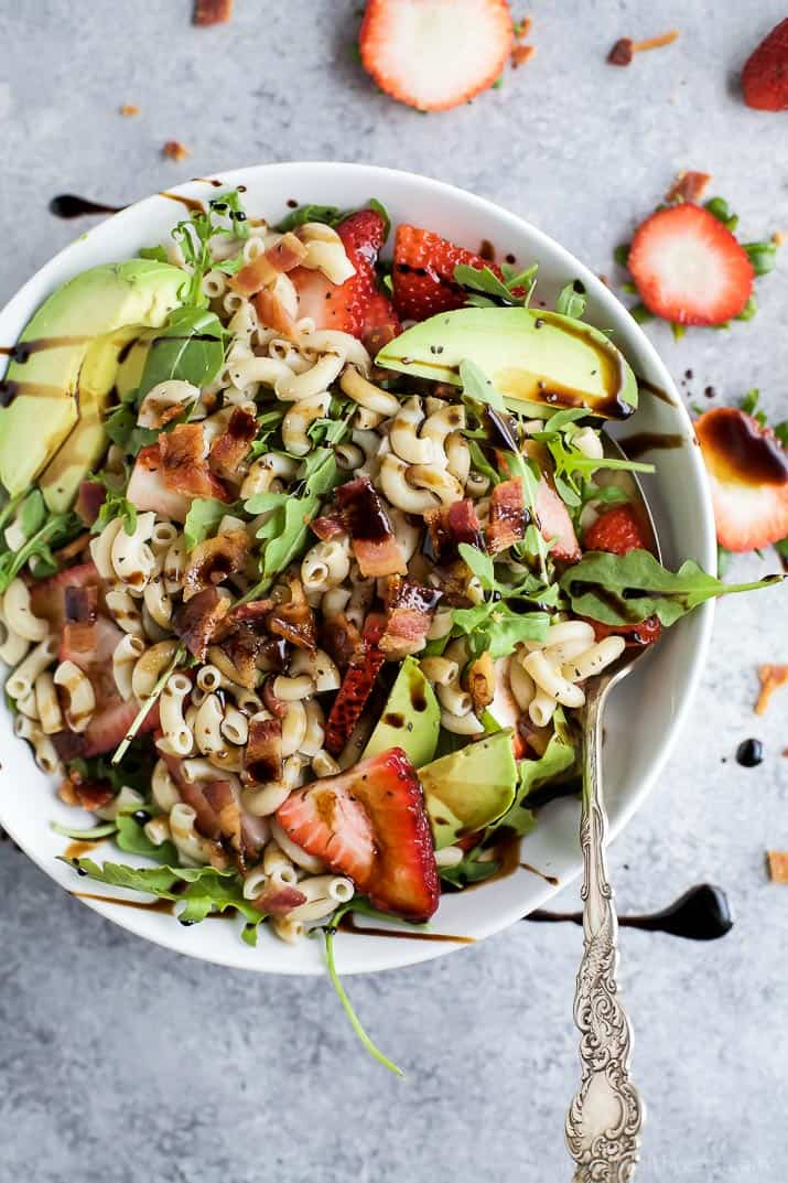 Easy Strawberry Avocado Pasta Salad tossed with fresh arugula, bacon, and a balsamic vinaigrette. The perfect pasta salad for those summer nights! | #ad | gluten free recipes